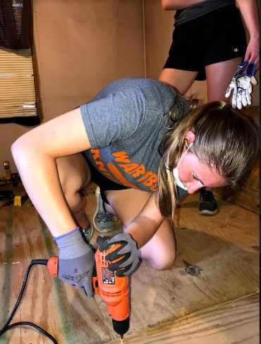 A student from Wartburg College in Waverly, Iowa volunteers on a WARM hurricane recovery rebuild as part of an alternative Spring break trip in April.